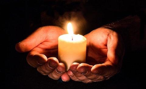 Tänt ljus i kupade händer