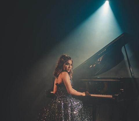 Finklädd tjej framför piano
